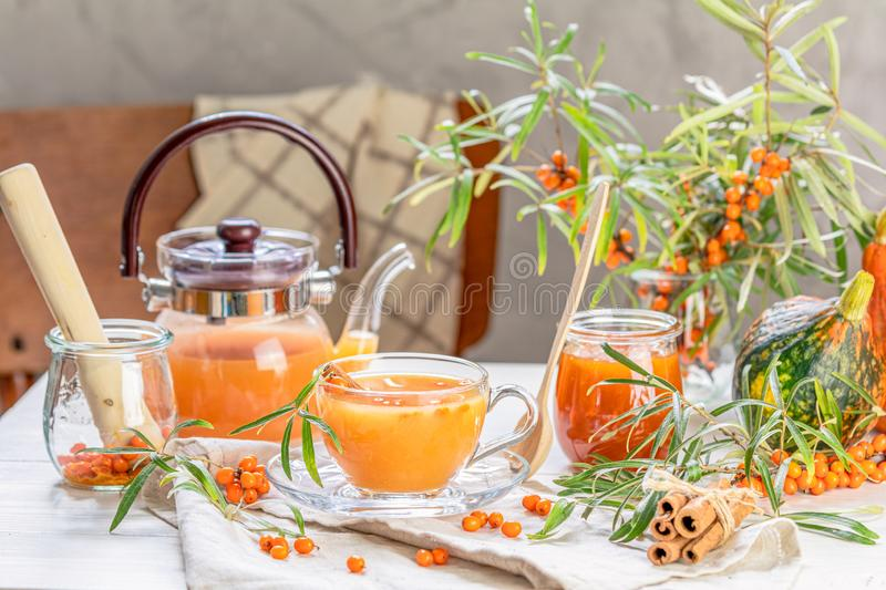Hot spicy tea with sea buckthorn in glass cup and teapot, selective focus, rustic light background. Cup and teapot of hot spicy tea with sea buckthorn, jam in stock photo