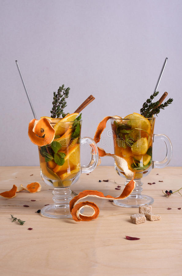 Hot spicy winter drink: cider, punch, tea with citrus, mint, cinnamon and thyme on wooden table. stock photos