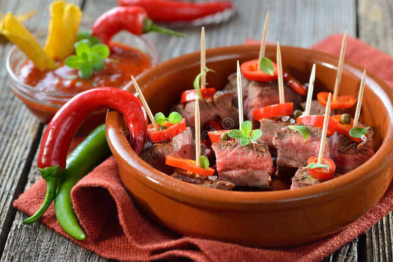 Hot steak tapas. Medium fried steak tapas with chili, peppers and hot dip sauce stock photo