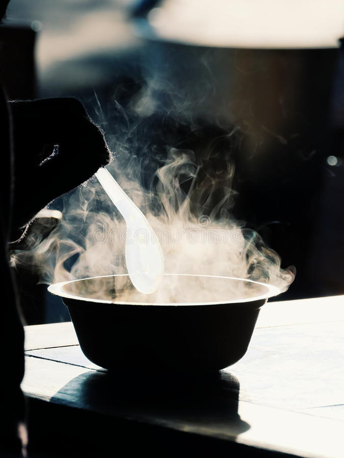 Hot steam of a congee bowl in cold weather royalty free stock photography