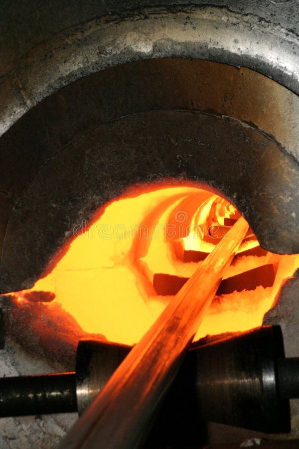 Hot steel. A hot steel bar exiting from a forge royalty free stock photo