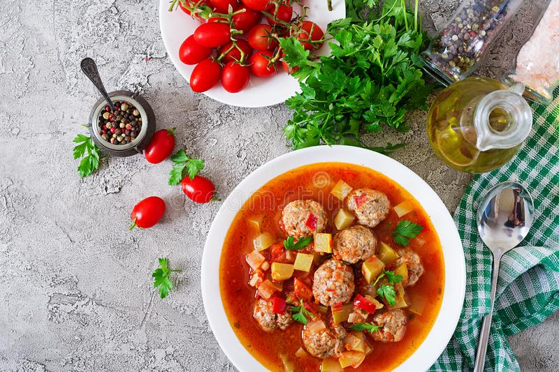 Hot stew tomato soup with meatballs and vegetables. Closeup in a bowl on the table. Albondigas soup, spanish and Mexican food. Top view. Flat lay royalty free stock photography