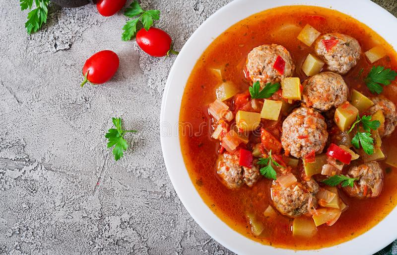 Hot stew tomato soup with meatballs and vegetables. Closeup in a bowl on the table. Albondigas soup, spanish and Mexican food. Top view. Flat lay royalty free stock image