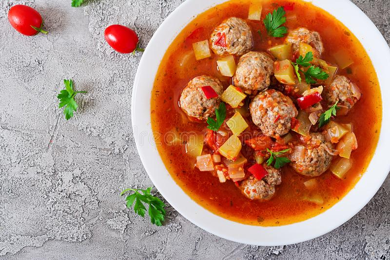 Hot stew tomato soup with meatballs and vegetables. Closeup in a bowl on the table. Albondigas soup, spanish and Mexican food. Top view. Flat lay royalty free stock images