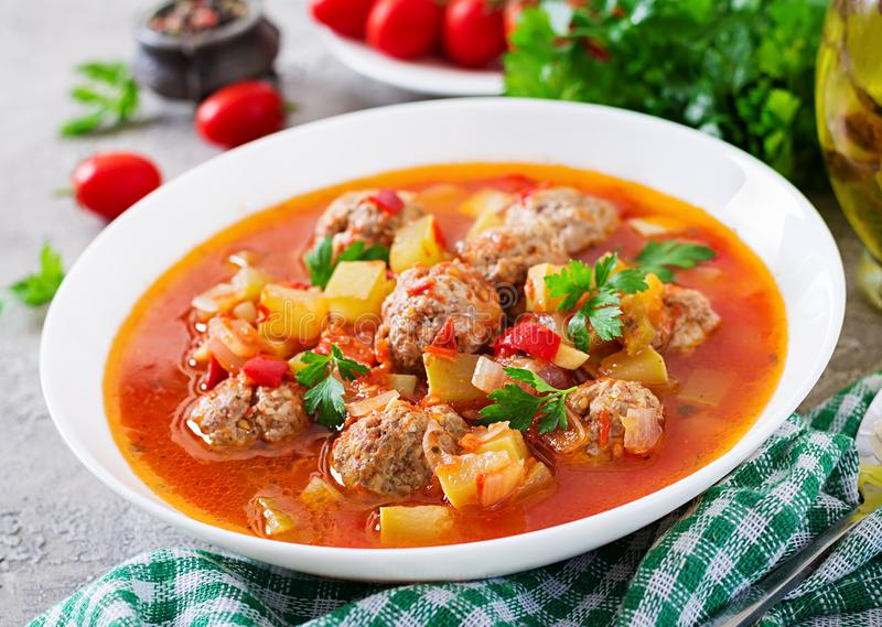 Hot stew tomato soup with meatballs and vegetables. Closeup in a bowl on the table. Albondigas soup, spanish and mexican food stock images