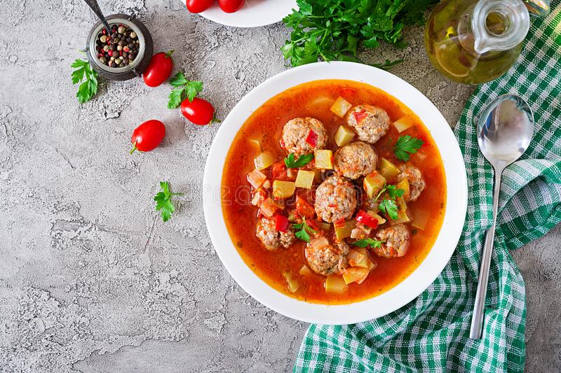 Hot stew tomato soup with meatballs and vegetables. Closeup in a bowl on the table. Albondigas soup, spanish and Mexican food. Top view. Flat lay stock photo
