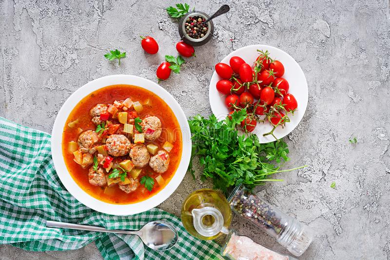 Hot stew tomato soup with meatballs and vegetables. Closeup in a bowl on the table. Albondigas soup, spanish and Mexican food. Top view. Flat lay stock photography
