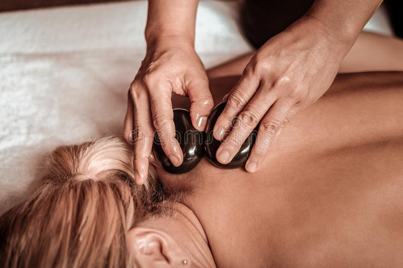 Hot stone neck massage for a tired woman. Warming the body. Hands of masseuse doing hot stone neck massage for a tired foman lying in front of her stock photos