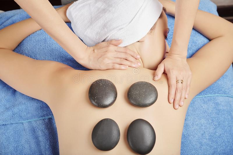 Hot stones massage. Masseur putting hot basalt stones on back of young women and massaging her neck and shoulders stock photos