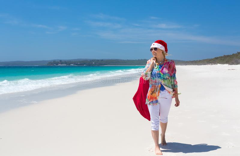 Christmas down on the beach summer sun female walking with santa royalty free stock images