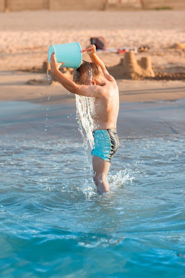 Hot summer - little boy splashing stock photo