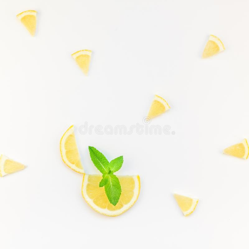 Hot summer refreshment lemonade idea. Square flatlay overhead top view citrus lemon slices and mint herbs leaves white table background with copyspace. Hot royalty free stock image