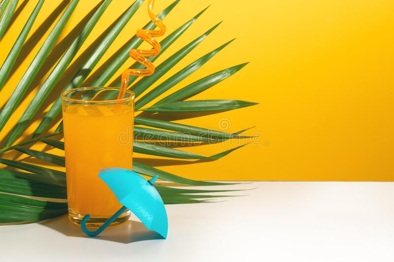 Hot summer season vacation holiday, fresh drink fruit orange juice, palm coconut leaf tree. Umbrella stock photography