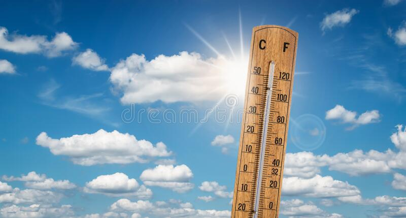Hot summer weather with extreme high temperatures concept. Wooden thermometer with high temperatures on a blue sunny sky with white clouds. Space for text stock photo