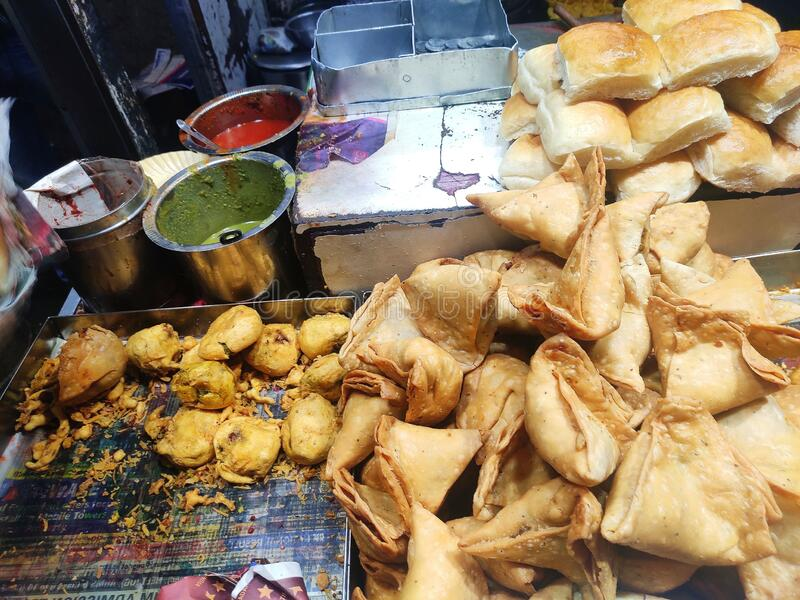 Hot tastey Indian Street food samosa and vada pav selling food. Hot tastey Indian Street food samosa and vada pav Indian snacks with green and red chutney side royalty free stock photos
