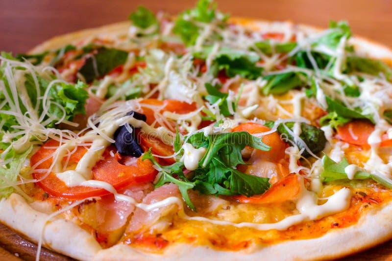Hot tasty pizza with arugula, tomatoes and bacon royalty free stock photo