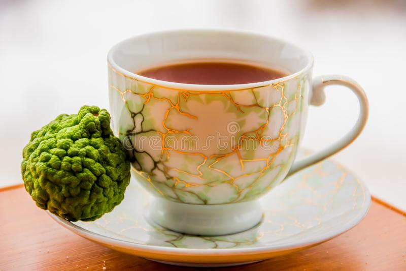 Hot tea with bergamot on wooden table in the cold. stock photos