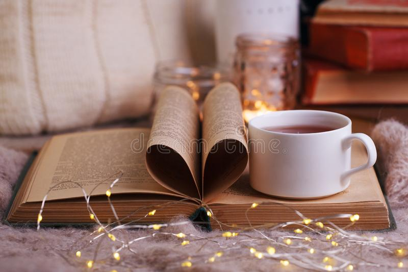 Hot tea and book with woolan plaid on wood background - seasonal relax concept. Autumn winter weekend still life background, cozy royalty free stock photos