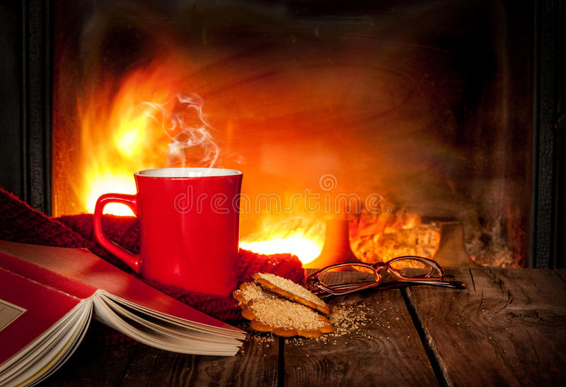 Hot tea or coffee in a red mug, book and fireplace. Hot tea or coffee in a red mug, ginger cookies, book and glasses on vintage wood table. Fireplace as