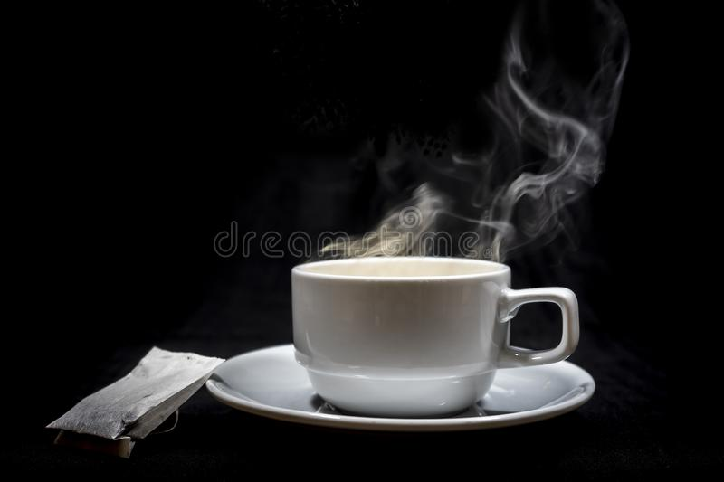 Hot tea in cup with steam, tea bag on black background royalty free stock image