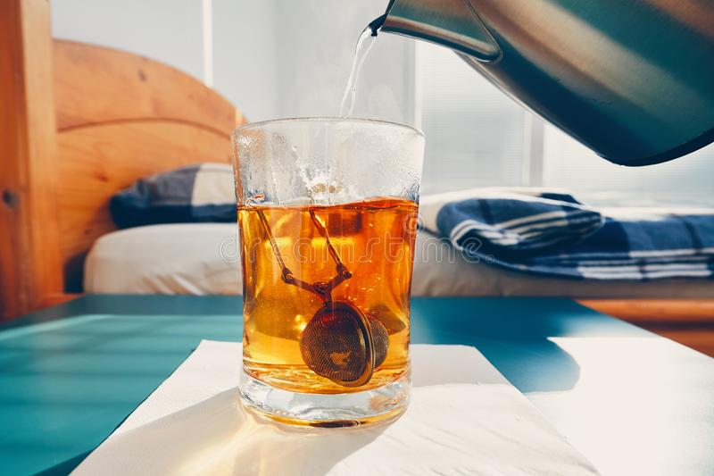 Hot tea in glass cup. On the bedside table in bedroom stock photo