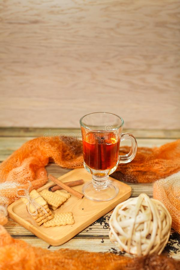 Hot Tea in glass cup with cinnamon sticks tea leaves and cookies on wooden table and knitted scarf around royalty free stock photos