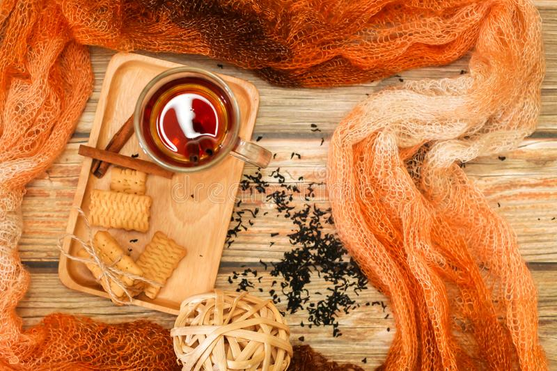 Hot Tea in glass cup with cinnamon sticks tea leaves and cookies on wooden table and knitted scarf around, flat lay stock photography