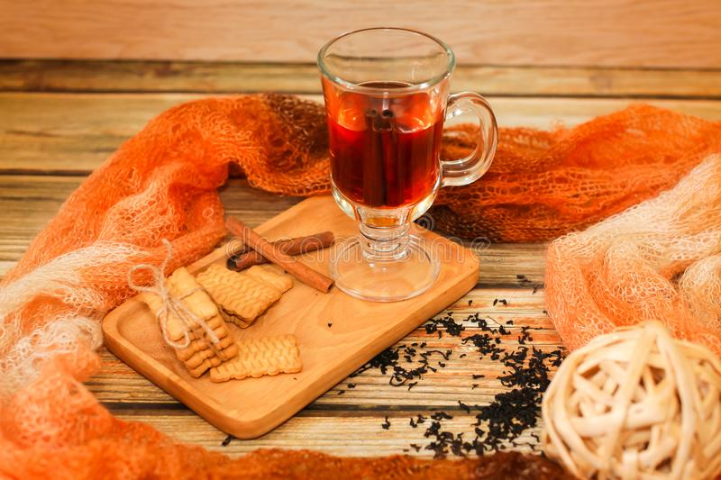 Hot Tea in glass cup with cinnamon sticks tea leaves and cookies on wooden table and knitted scarf around royalty free stock photography