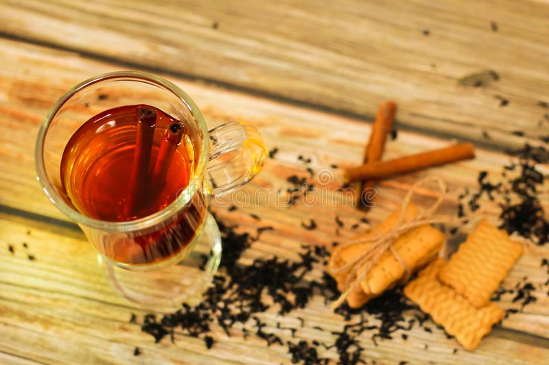 Hot Tea in glass cup with cinnamon sticks tea leaves and cookies on wooden table, top view royalty free stock image