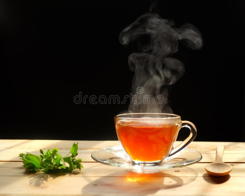 Hot tea in glass cup with steam and lemon .tea leaves and mint herb on wood background royalty free stock photo