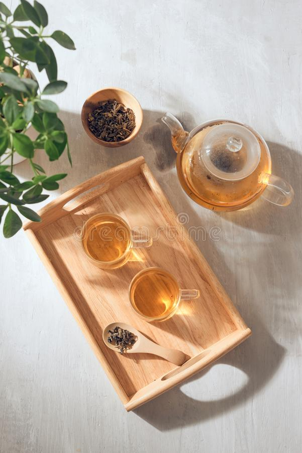 Hot tea is in the glass. Placed on a wooden tray.  stock photography