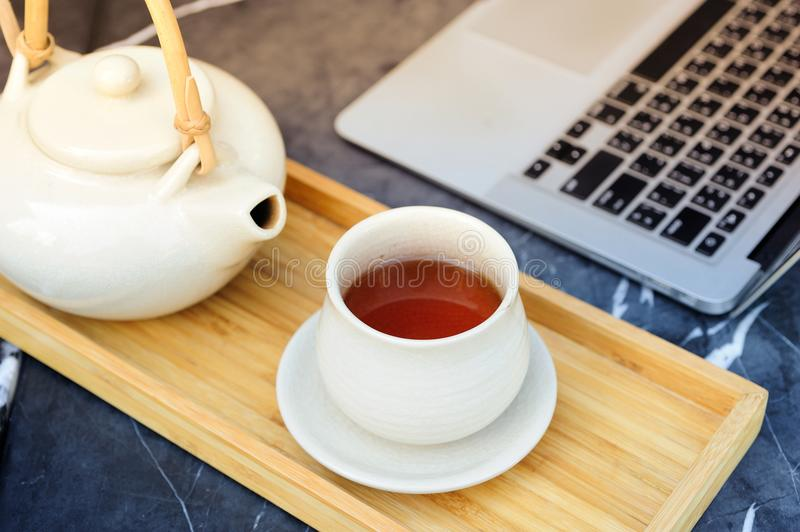 Hot tea is in a glass on a wooden traynear computer. Hot tea is in the glass. Placed on a wooden tray. For a moment of rest of the day. After a tiring work royalty free stock photo