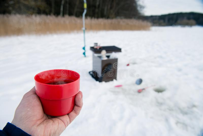 Hot tea in hand of the fisherman, a picnic stock image