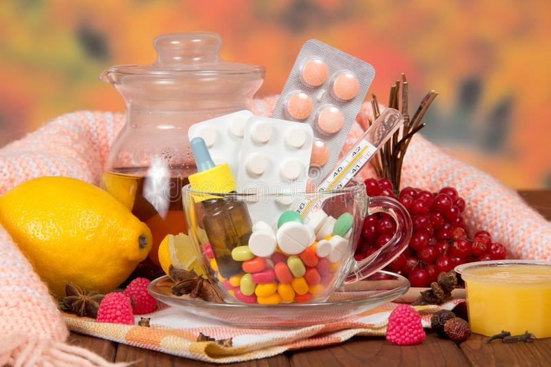 Hot tea with honey and lemon in the pitcher, pills catarrh, warm scarf on table stock photos