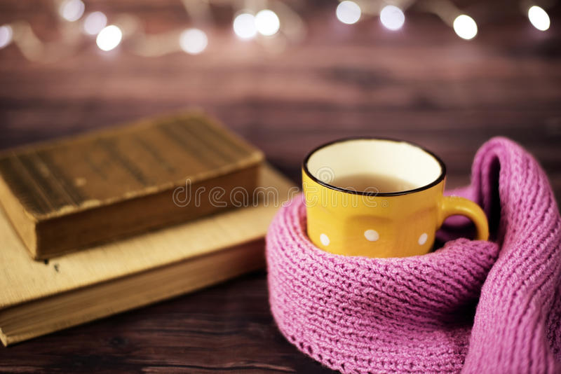 Hot tea, hot chocolate, coffee in yellow cup, wrapped with a pink knitted scarf. Old books. Blurred lights, wooden background. Winter time, Rustic background royalty free stock image