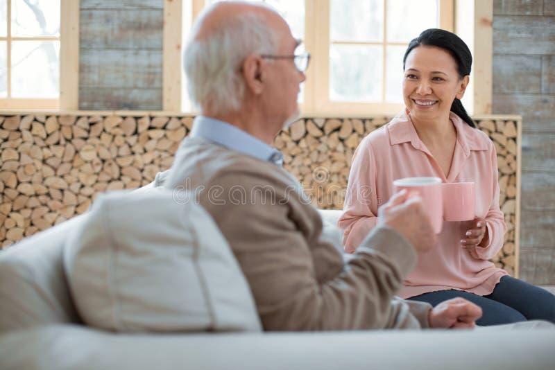 Cheerful caregiver and senior man drinking tea royalty free stock photo