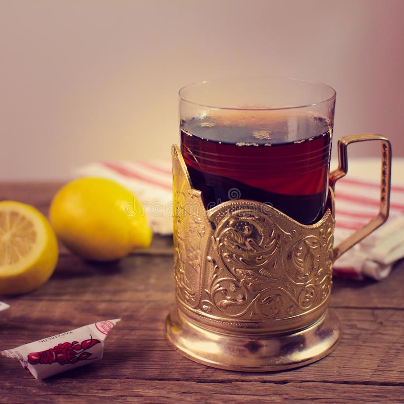 Hot tea in glassholder. Hot tea, lemon, candy stock images