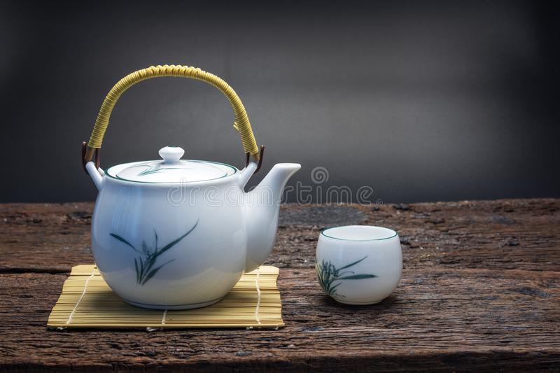 Hot tea pot on bamboo mat with cup on wooden table royalty free stock photography