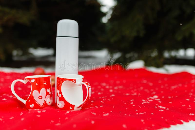 Hot tea spilled into red heart-patterned mugs. White thermos with tea and red apples on a red picnic blanket. Winter picnic in the woods in the mountains royalty free stock photos