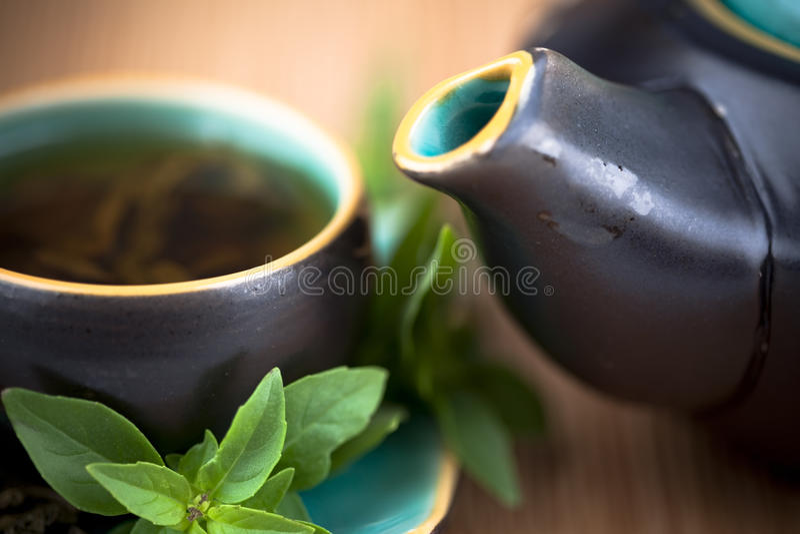 Hot tea and tea pot. A cup of hot tea, tea pot and tea leaves stock photo