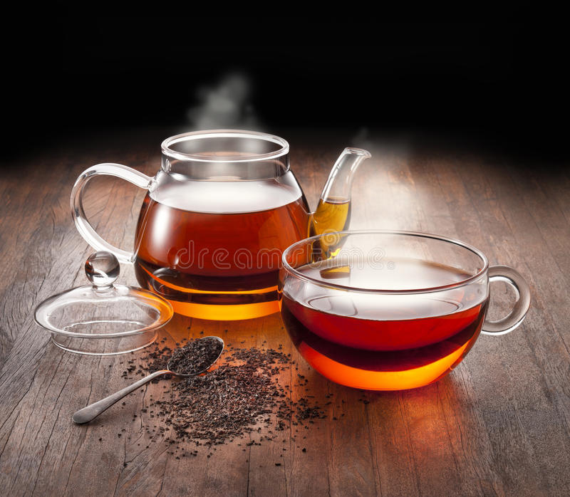 Hot Tea Teapot Cup. A teapot and teacup full of steaming hot tea on a rustic wood background