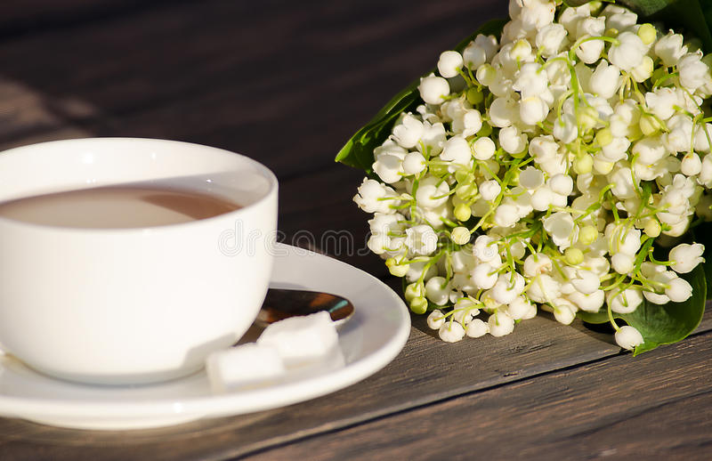 Hot tea in a white cup with a bouquet of flowers stock photography