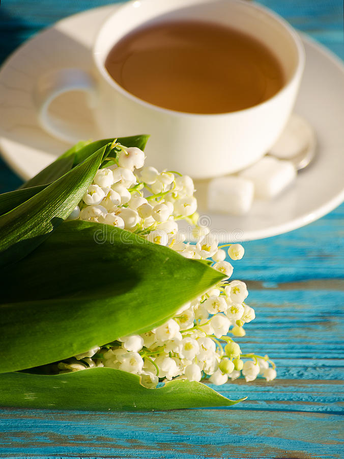 Hot tea in a white cup with a bouquet of flowers royalty free stock photo