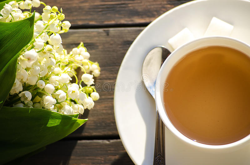 Hot tea in a white cup with a bouquet of flowers royalty free stock images