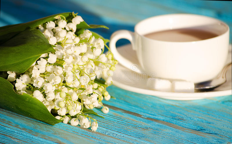 Hot tea in a white cup with a bouquet of flowers stock photos