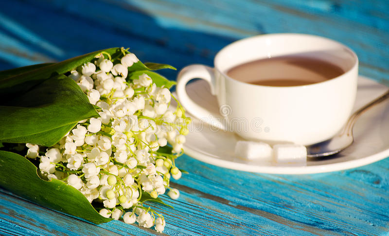 Hot tea in a white cup with a bouquet of flowers stock image