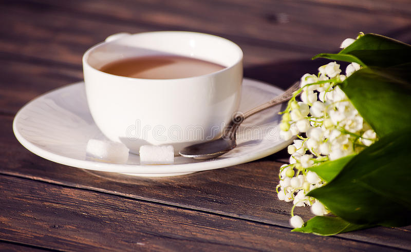 Hot tea in a white cup with a bouquet of flowers royalty free stock photography