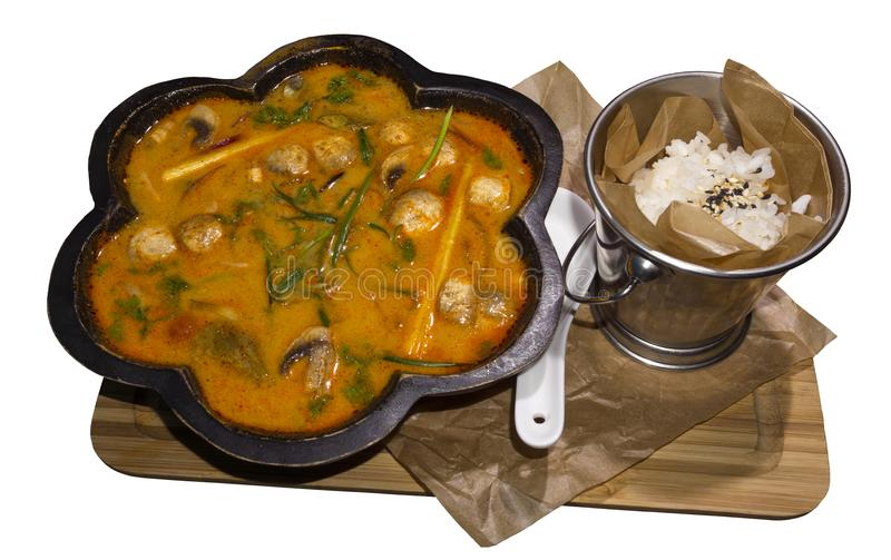 Thai soup tom yam in a figured wooden plate and a bucket of rice royalty free stock photos