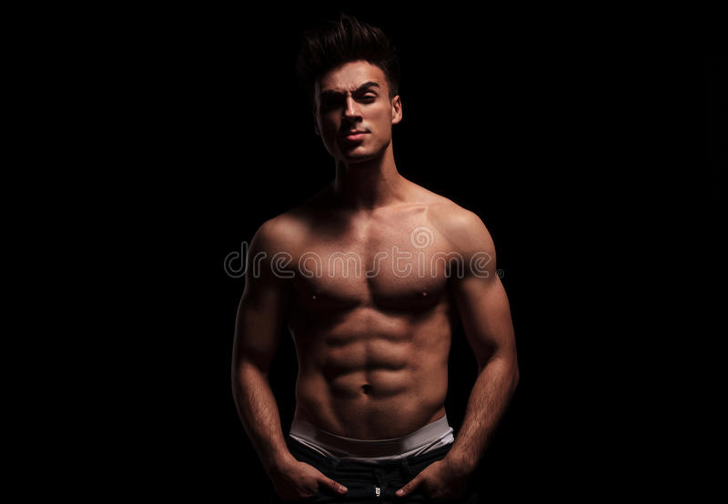 Hot, topless, muscular man posing with hands in pockets. Portrait of hot, topless, muscular man posing with hands in pockets while looking at the camera in dark royalty free stock image
