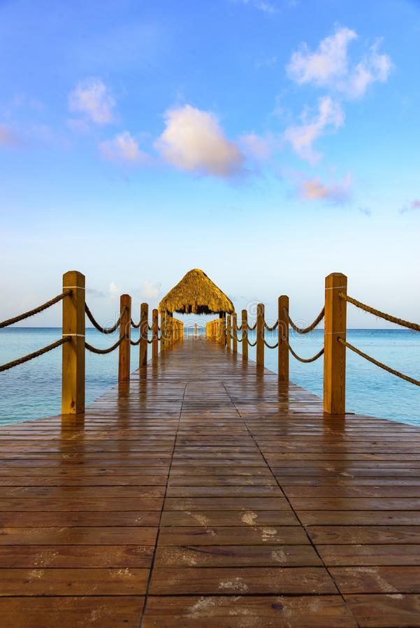 Hot tropical day the Caribbean sea pier with pergola. Palm leaves stock photography